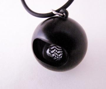 Pendant Ebony with Loose rolling Zebra shell in resin sphere : $120